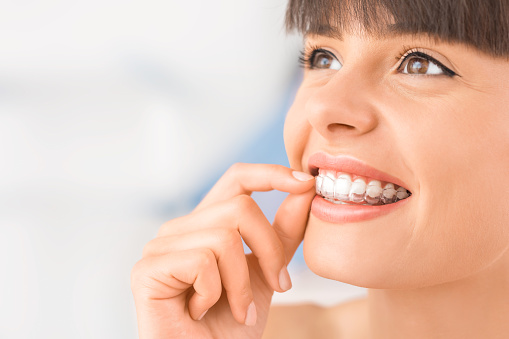 A smiling woman wearing Invisalign.