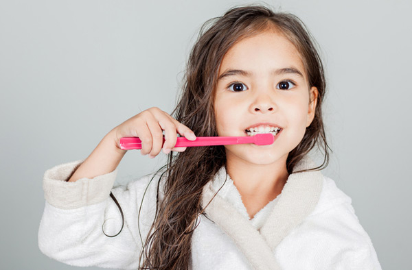 Young girl brushing her teeth at Premier Dental.